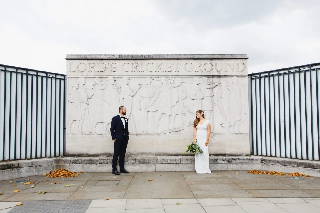 A bride and groom pose in front of Lords Cricket Ground at their wedding