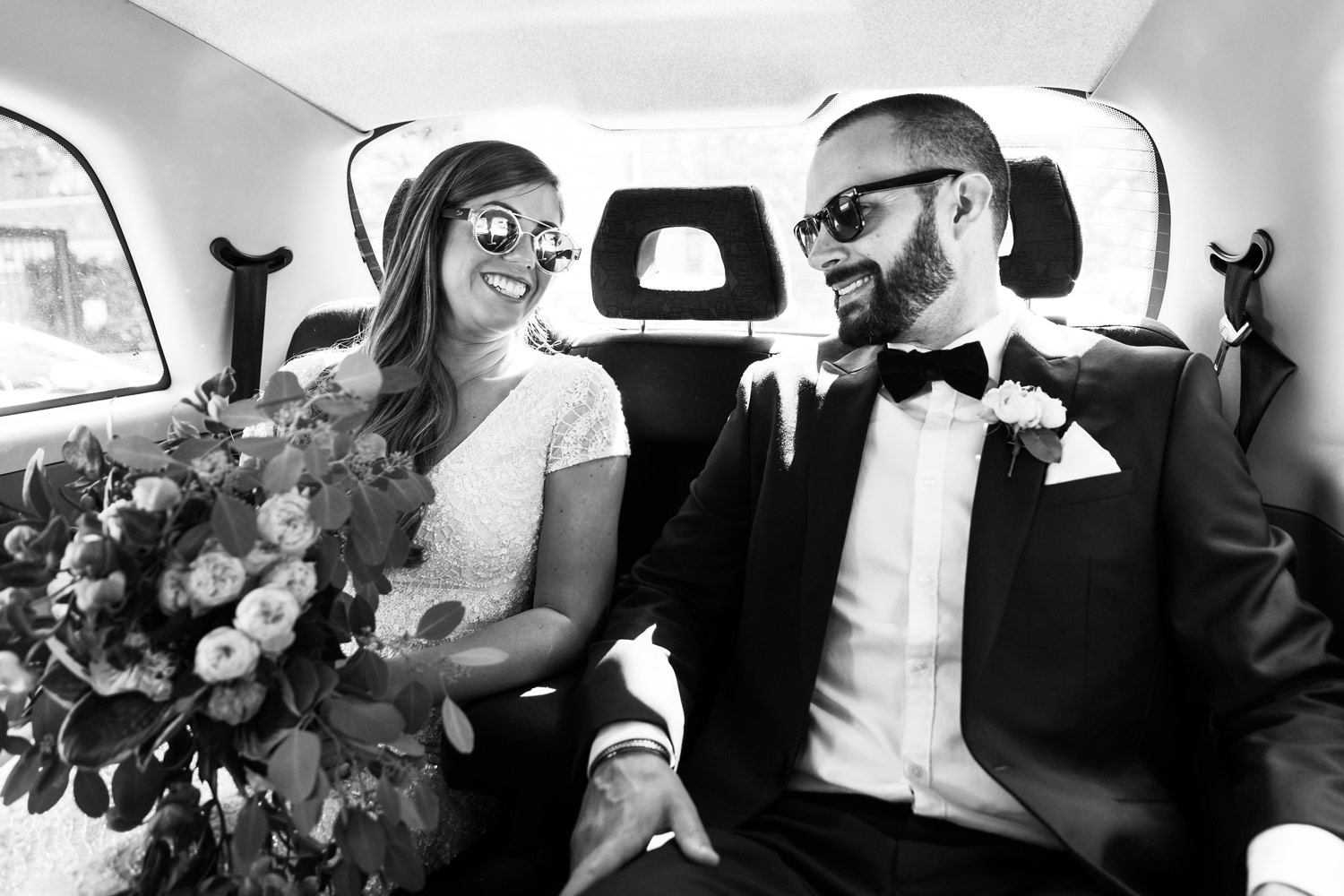 A wedding couple pose in sunglasses in the taxi after their wedding at Asia House in London.