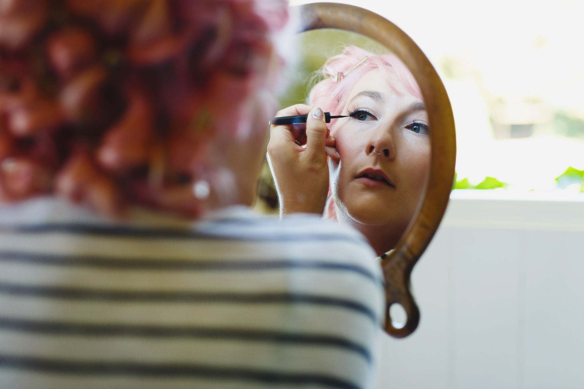 A bride does her eyeliner in a mirror