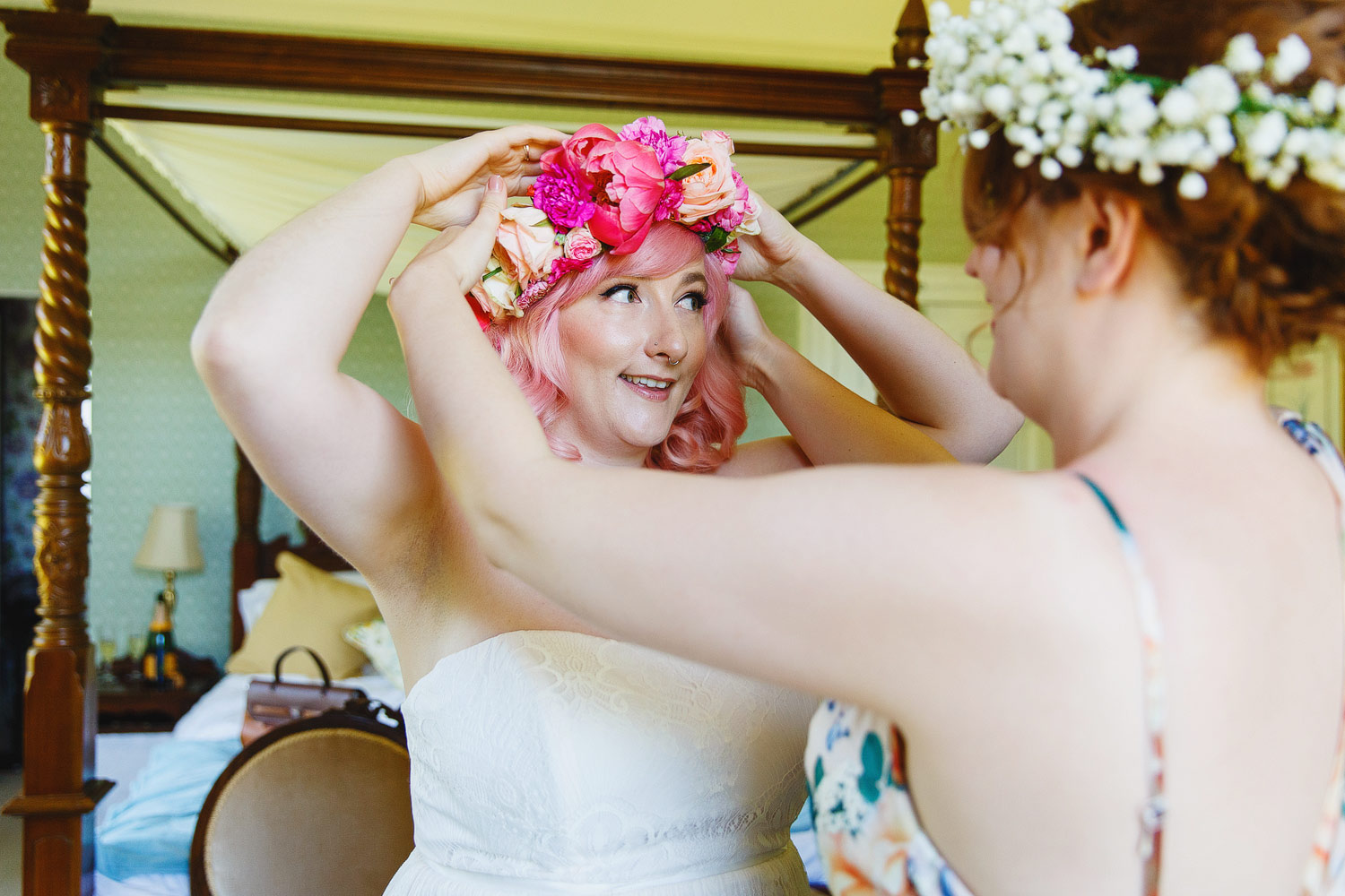 A bride puts on her floral crown at her wedding at Bressingham hall