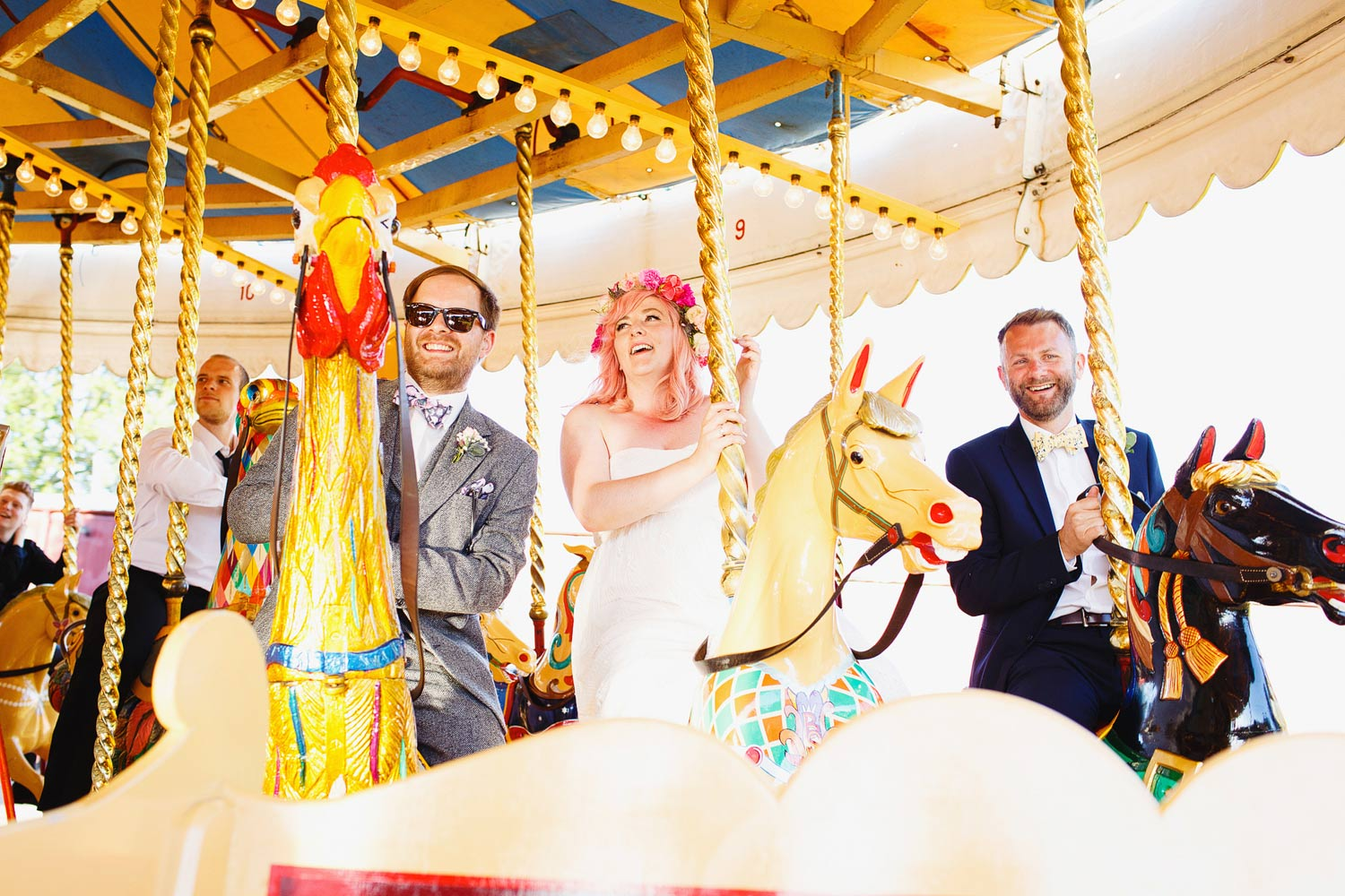 A bride and groom ride a carousel