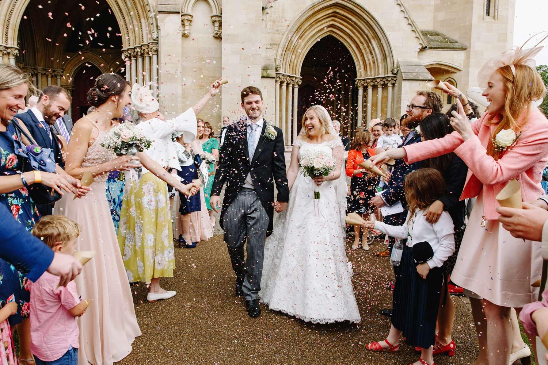 a couple walk through confetti at their wedding at Brocket Hall