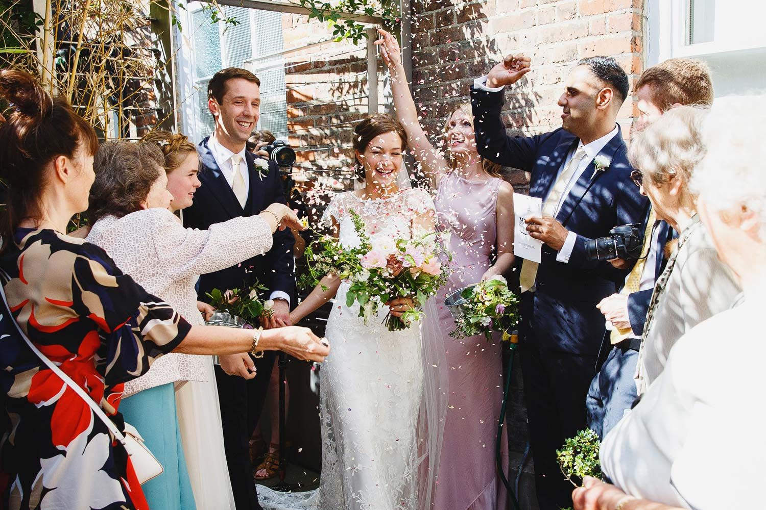A bride and groom walk through confetti at Burgh House Museum - London wedding photographer