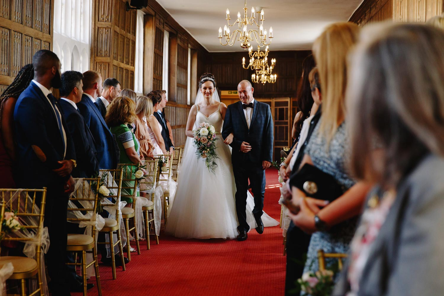 A bride and her fatehr walk down the aisle at Gosfield Hall