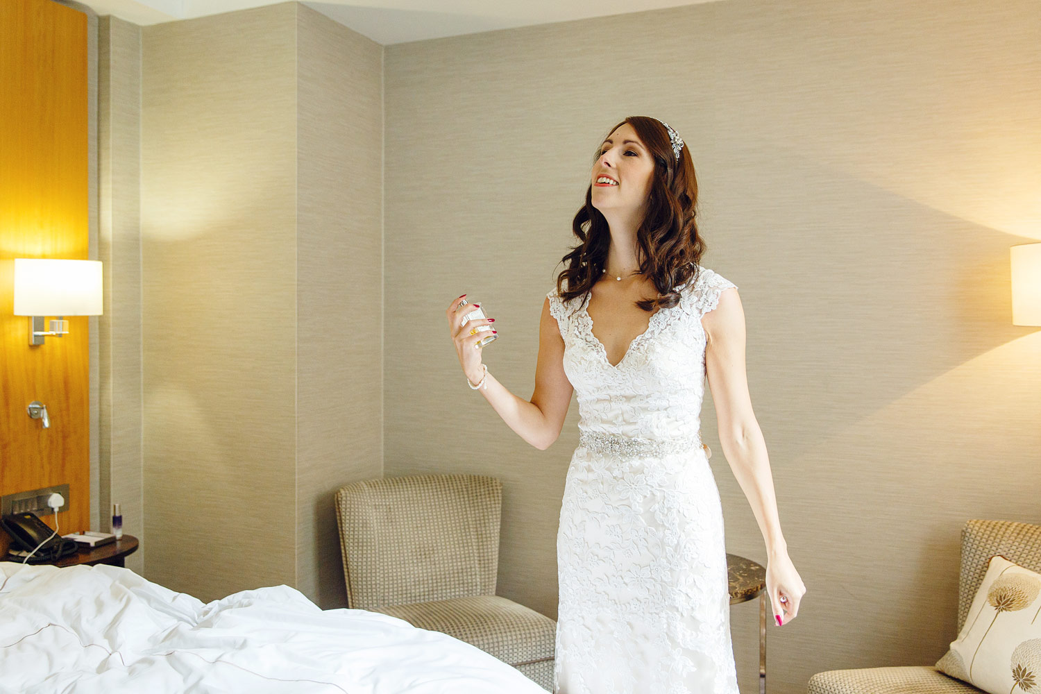 A bride sprays Jo Malone perfume and wears a Kenneth Winston Dress at the Conrad St James Hotel