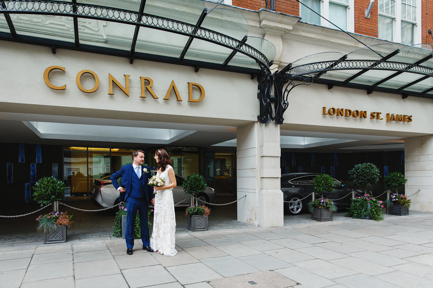 A wedding couple stand outside the Conrad St James Hotel - London wedding photographer