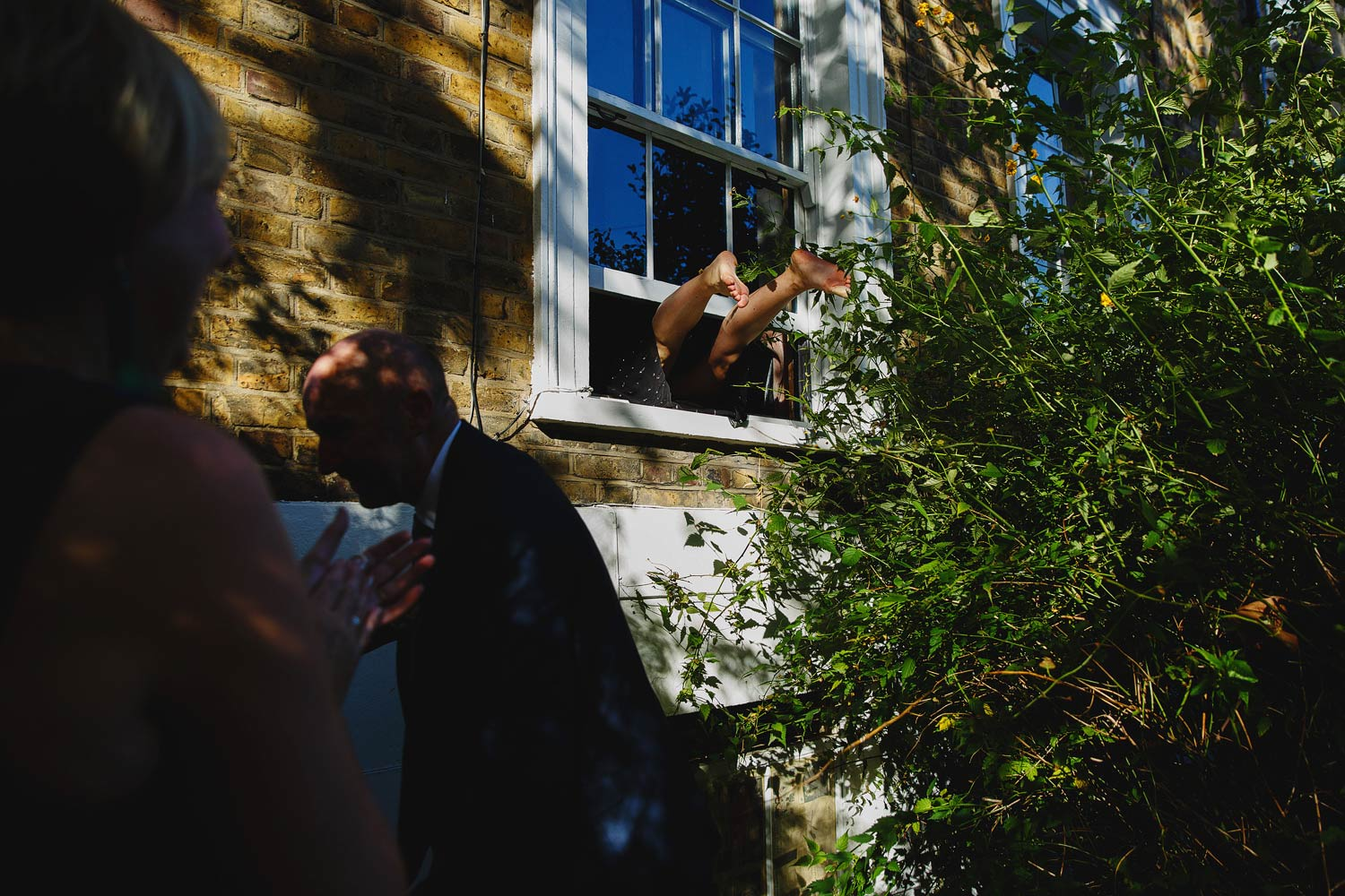 A bridesmaid climbs through the wedding after everyone gets locked out of the airbnb