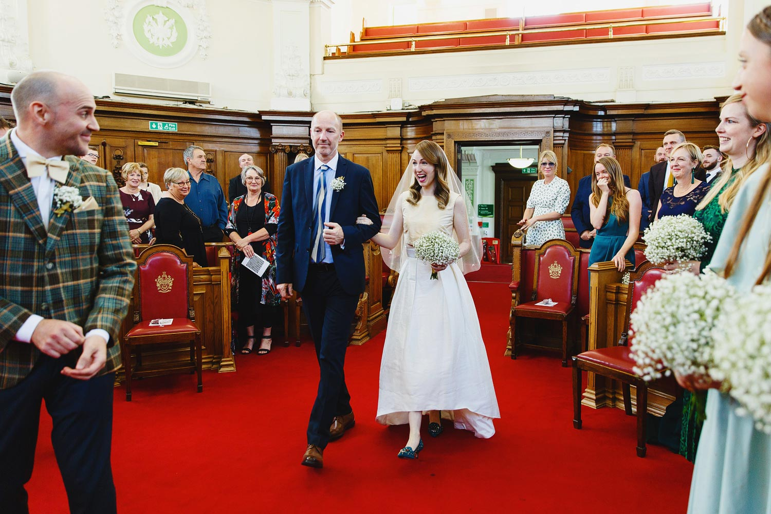 A bride and her father walk down the aisle at her Islington Town Hall wedding