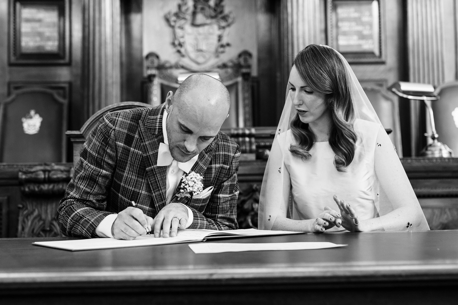 a bride and groom sign the register at Islington Town Hall