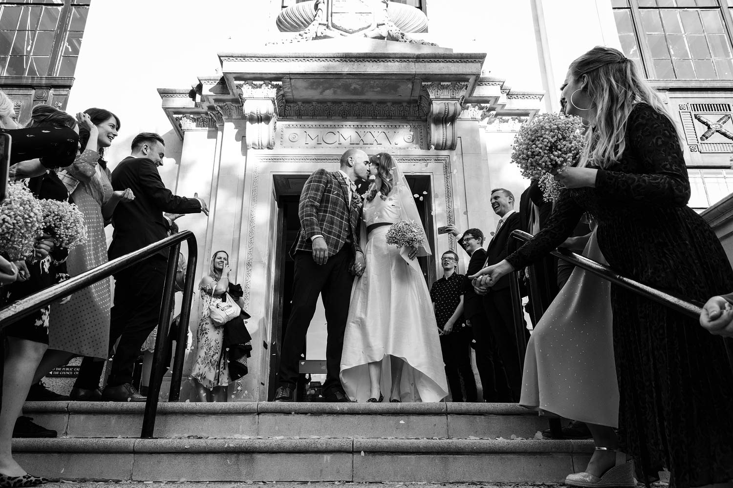 A couple walk through confetti at the Islington Town Hall