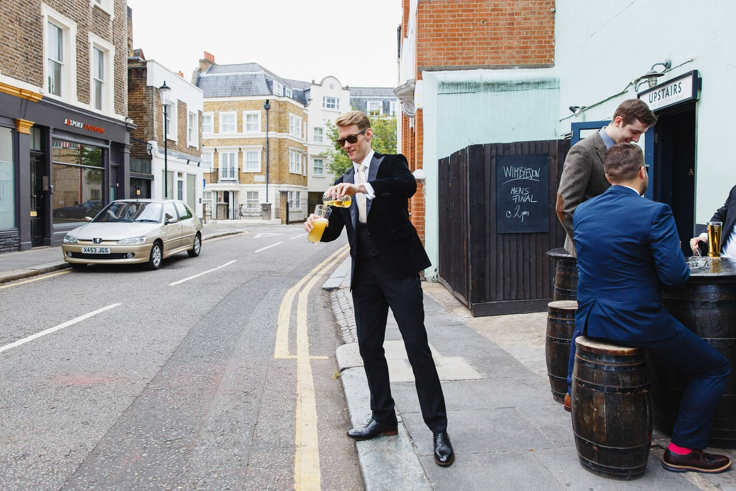 A groom pours a beer at the Roof Gardens in Kensington - London wedding photographer