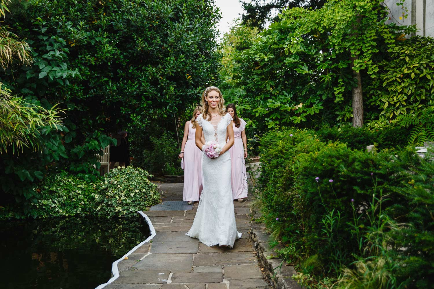 A bride prepares to walk to the ceremony at the Roof Gardens in Kensington - London wedding photographer