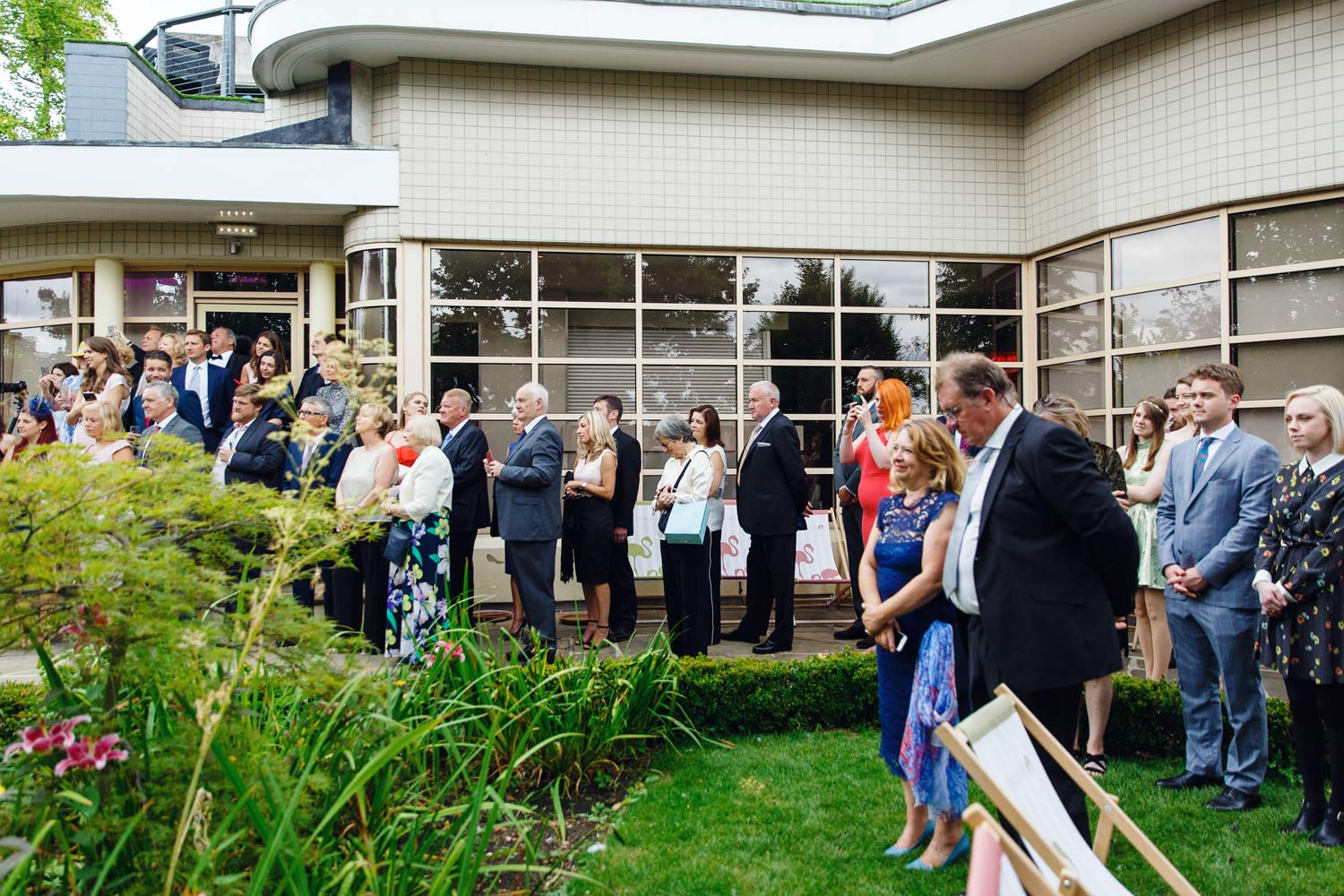 Guests watch the wedding ceremony at the Roof Gardens in Kensington - London wedding photographer