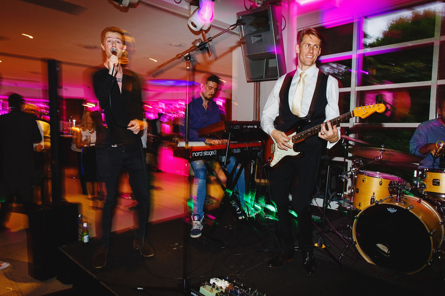 The groom plays guitar onstage at the Roof Gardens in Kensington - London wedding photographer