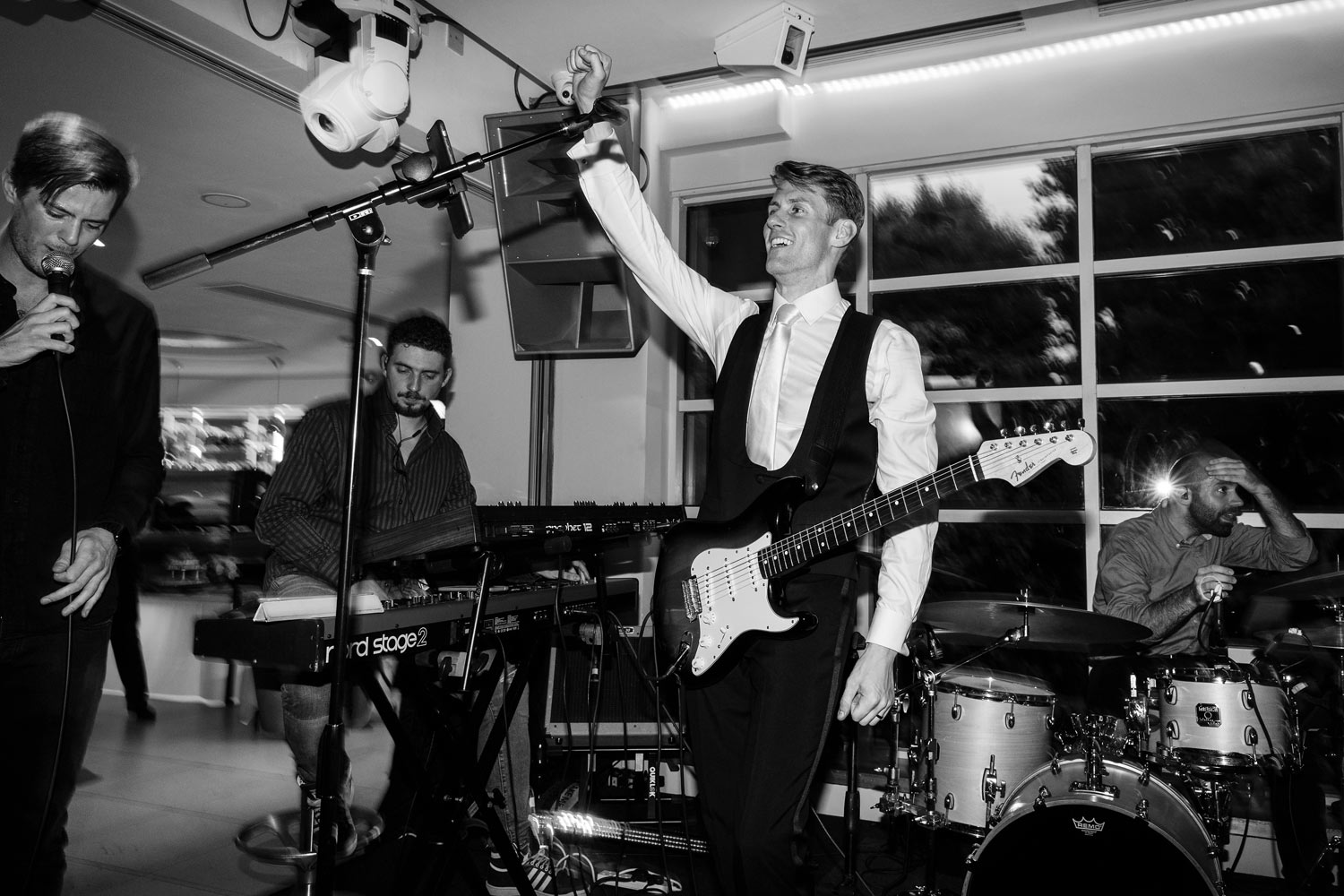 The groom plays guitar at the Roof Gardens in Kensington - London wedding photographer