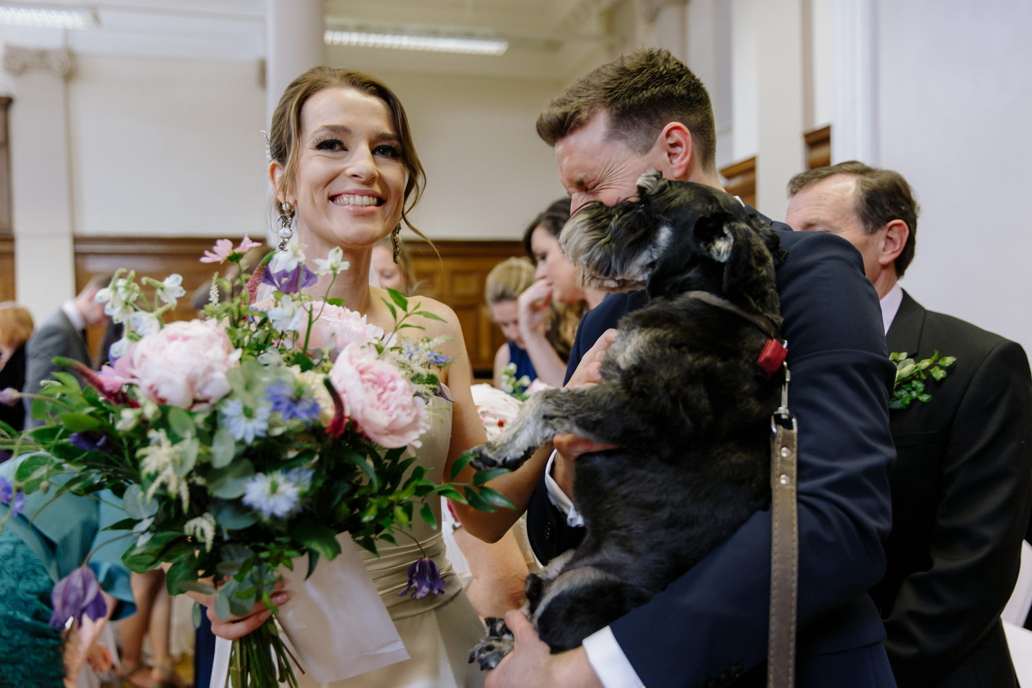 A bride and groom hold their dog at their wedding
