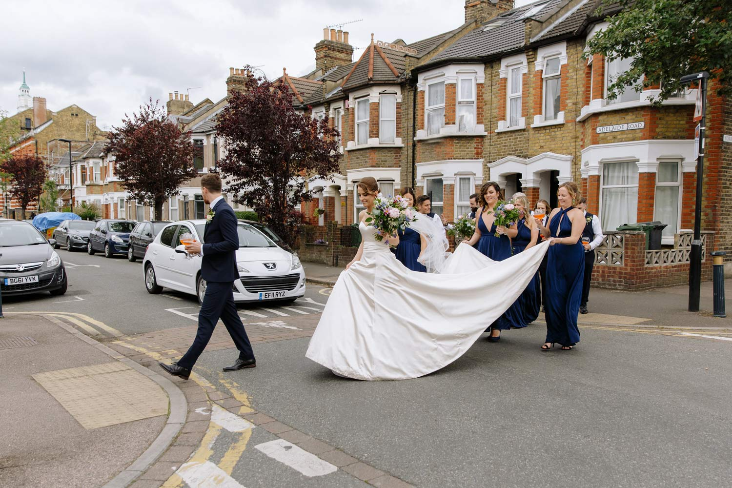 a bride and groom cross the road in Leyton, London