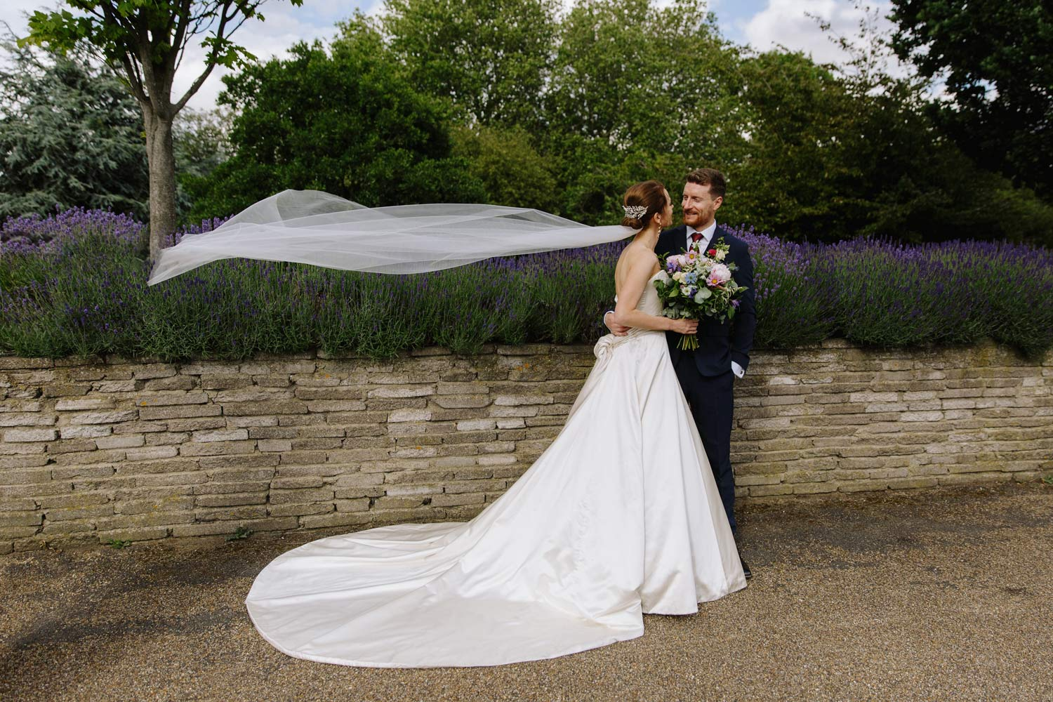 A bride and groom pose as the bride's veil blows in the wind.
