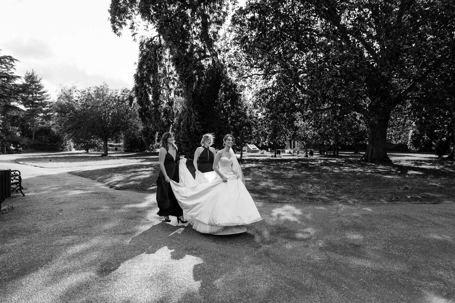 A bride walks through an East London park.
