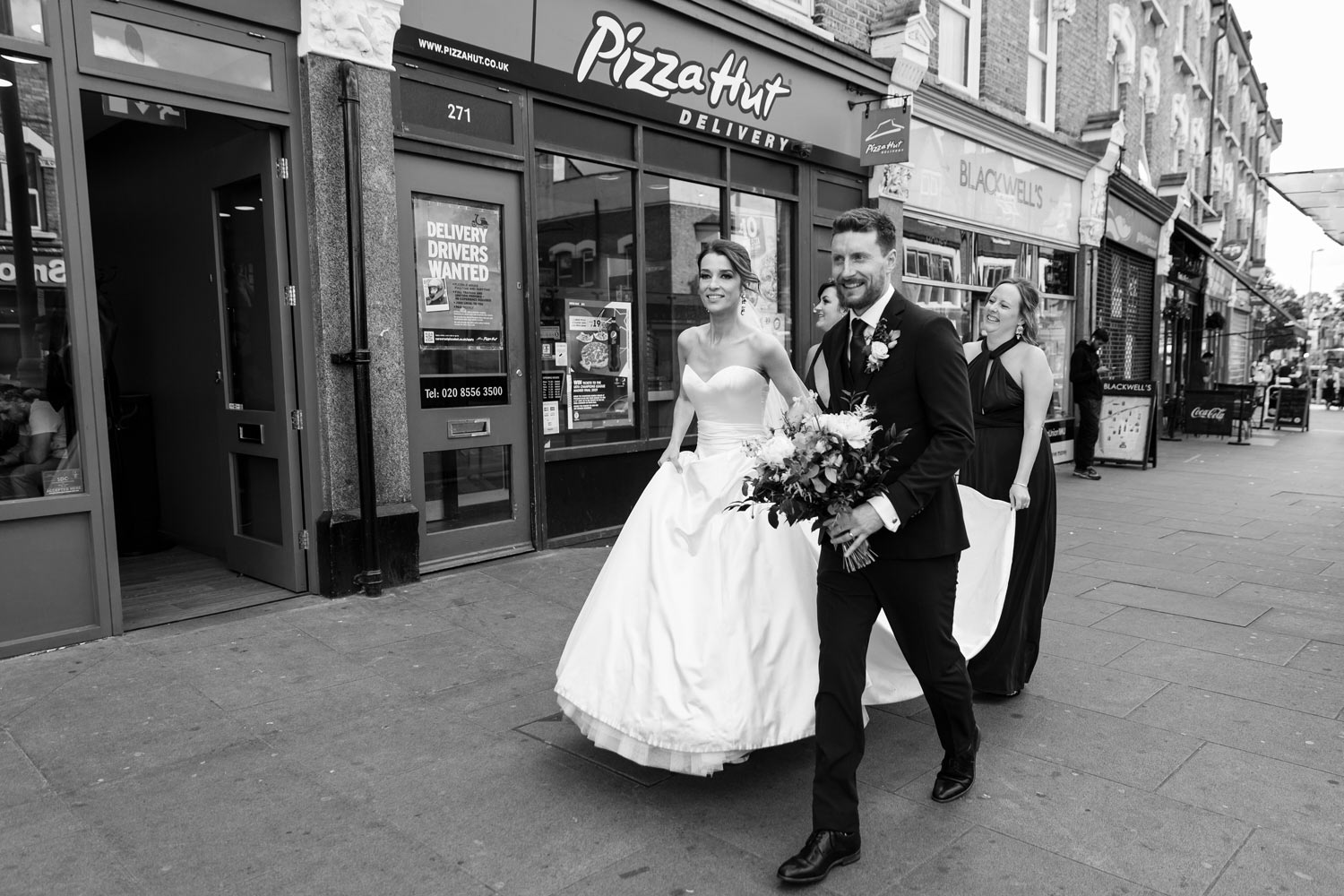 A bride and groom walk past a Pizza Hut.