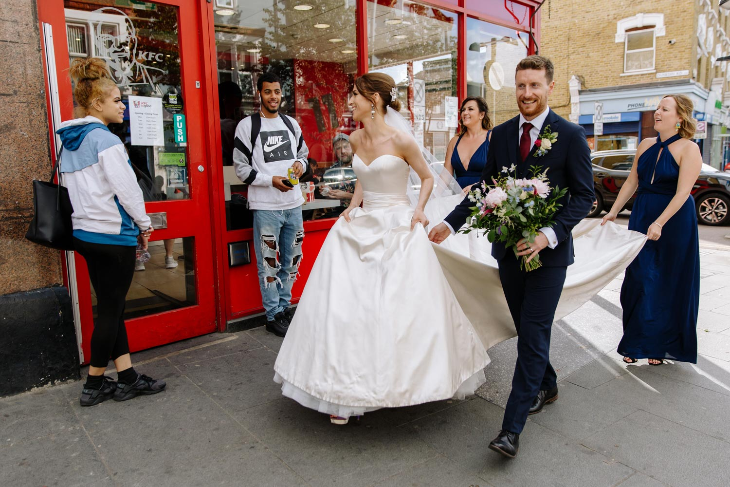 A bride and groom walk past a Pizza Hut in Leyton
