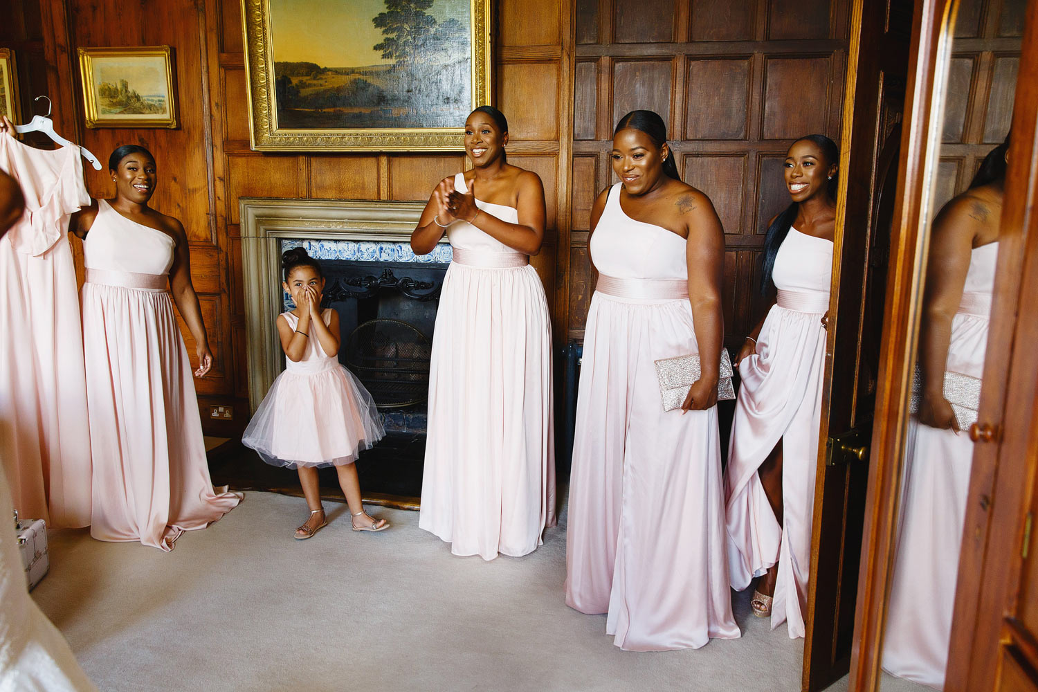 Bridesmaids see the bride in her dress for the first time at her Elmore Court wedding in The Cotswolds.