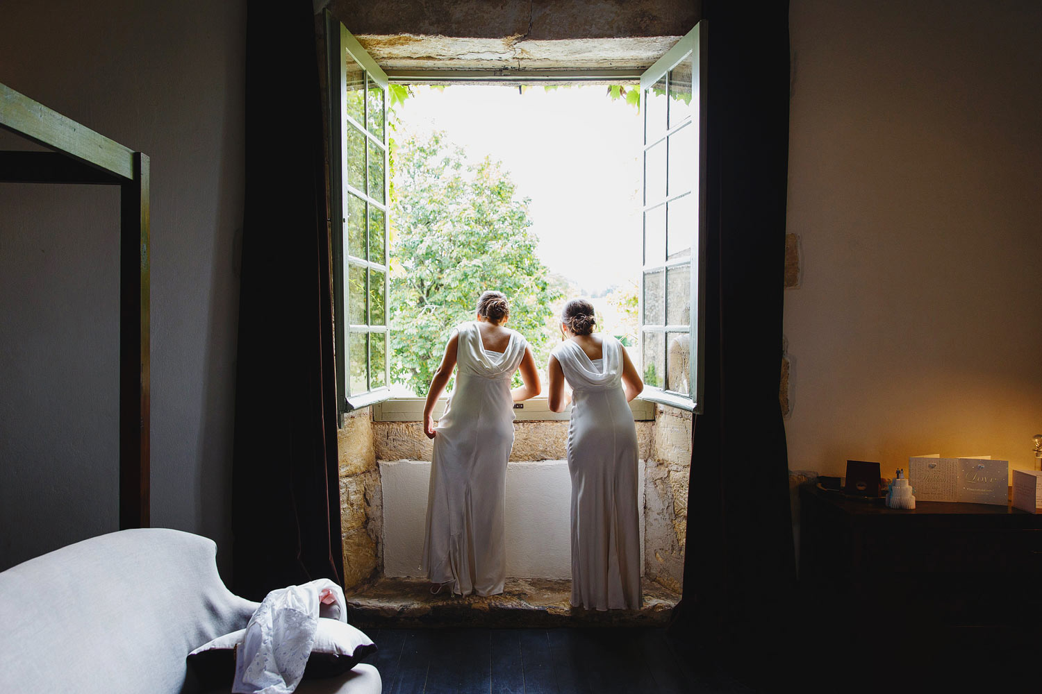 Bridesmaids look out of the bridal suite window at a Chateau Rigaud wedding