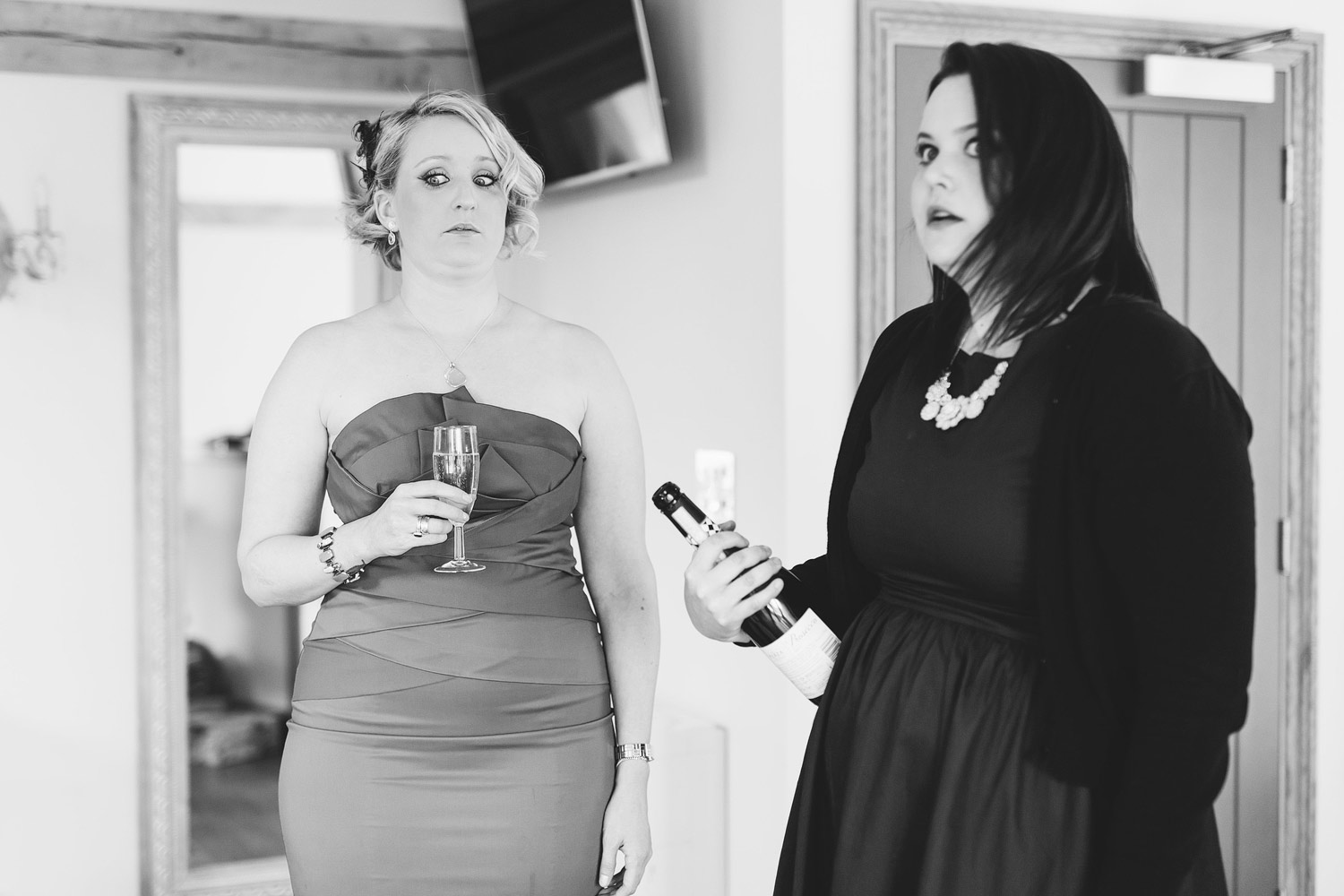 Two bridesmaids pull funny faces at a wedding at Cooling Castle Barn