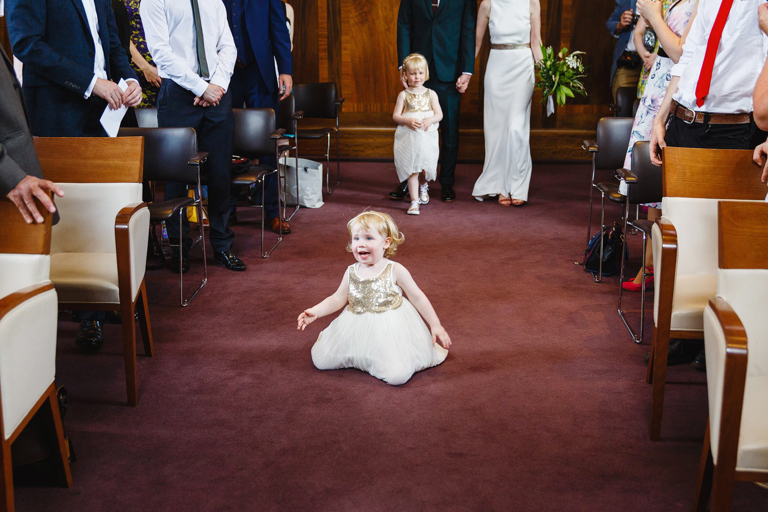 A flower girl falls down in the aisle at Stoke Newington Town Hall - London wedding photographer