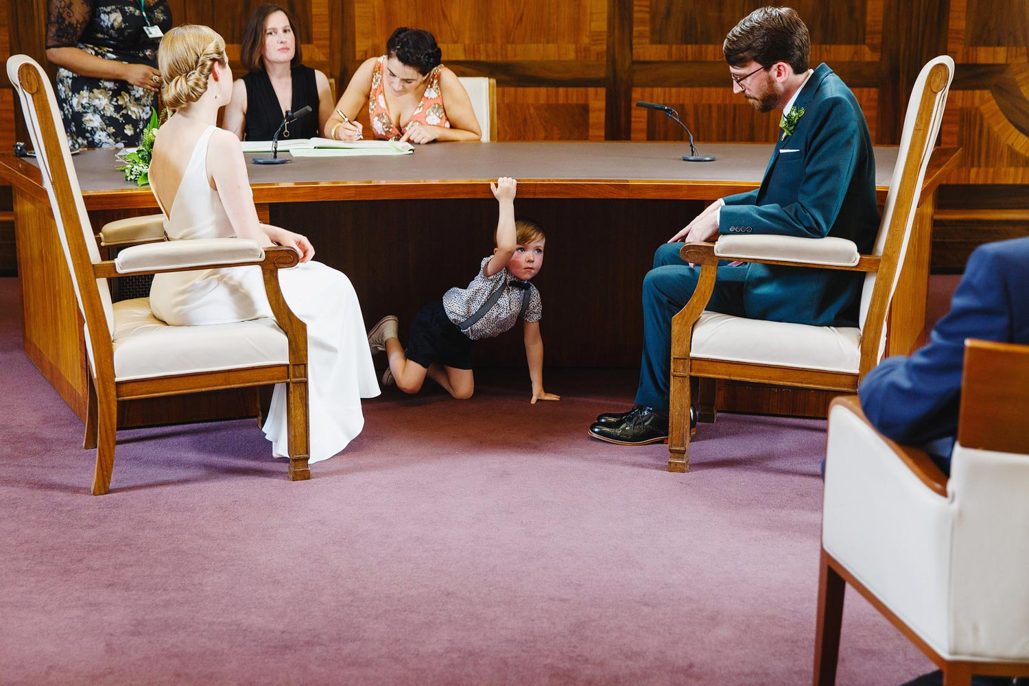 London wedding photographer - a child hides under the table at the Stoke Newington Town Hall