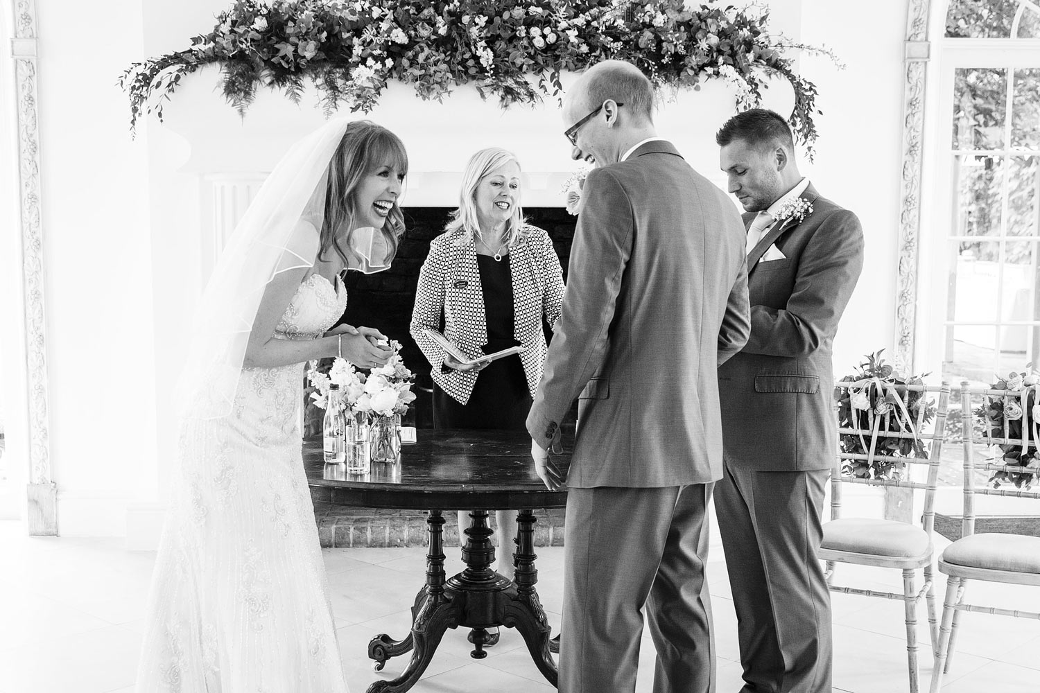 Bride and groom laughing while signing the register at Northbrook Park - Surrey wedding photographer
