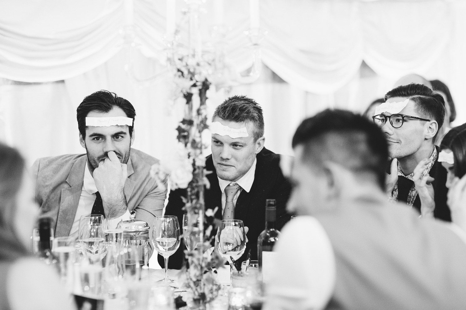 Guests play a game with paper stuck to their foreheads while at a wedding