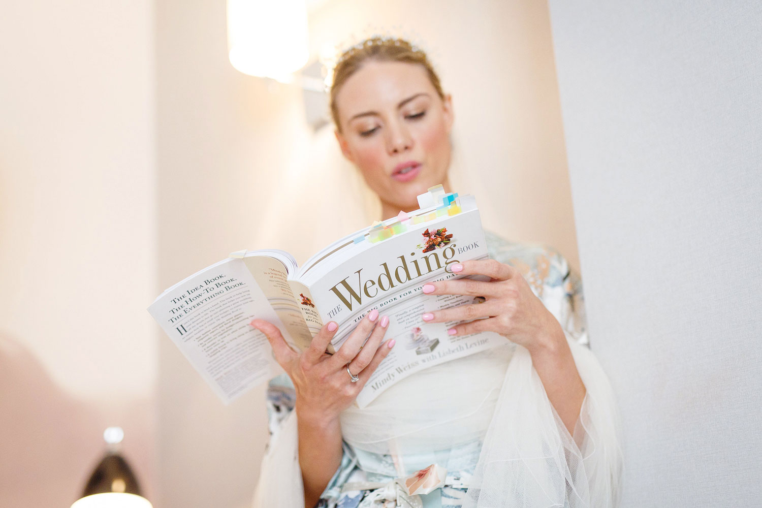 The bride studies a Wedding etiquette book before her wedding at the Roof Gardens in Kensington - London wedding photographer