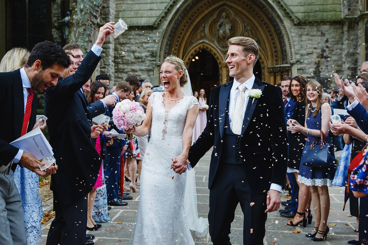 The bride and groom have confetti thrown at them at St Mary's Abbotts in Kensington