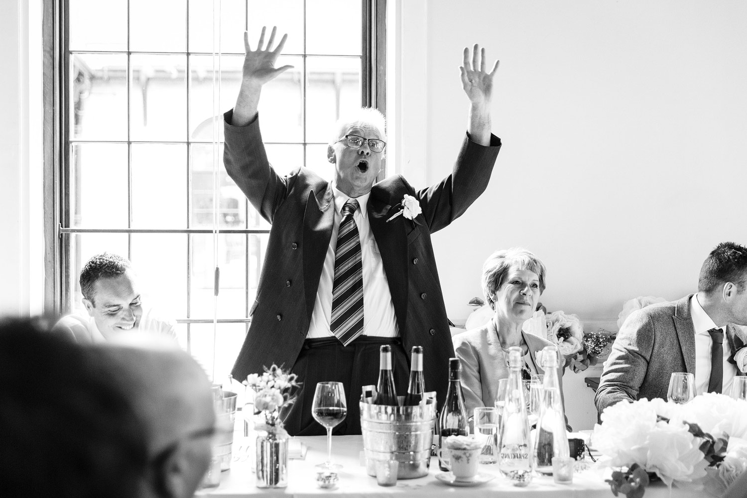 Father of the groom stands up and dances during speeches at a wedding at The Brewery in Moorgate - London wedding photographer