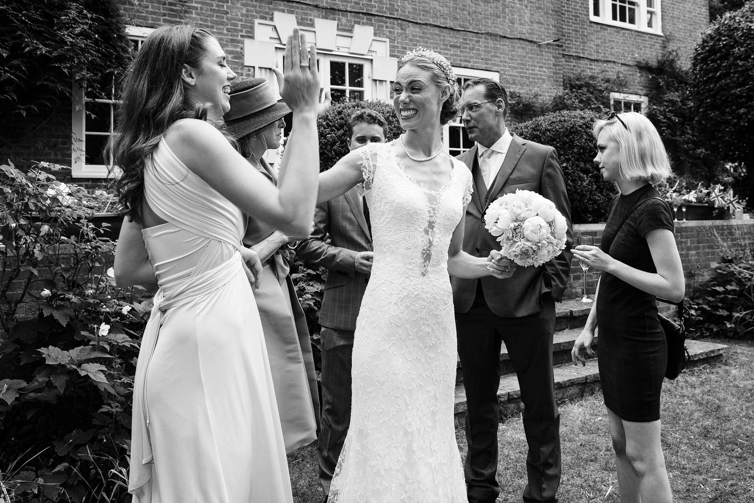 The bride high fives her bridesmaid at her wedding at the Vicarage in Kensington - London wedding photographer