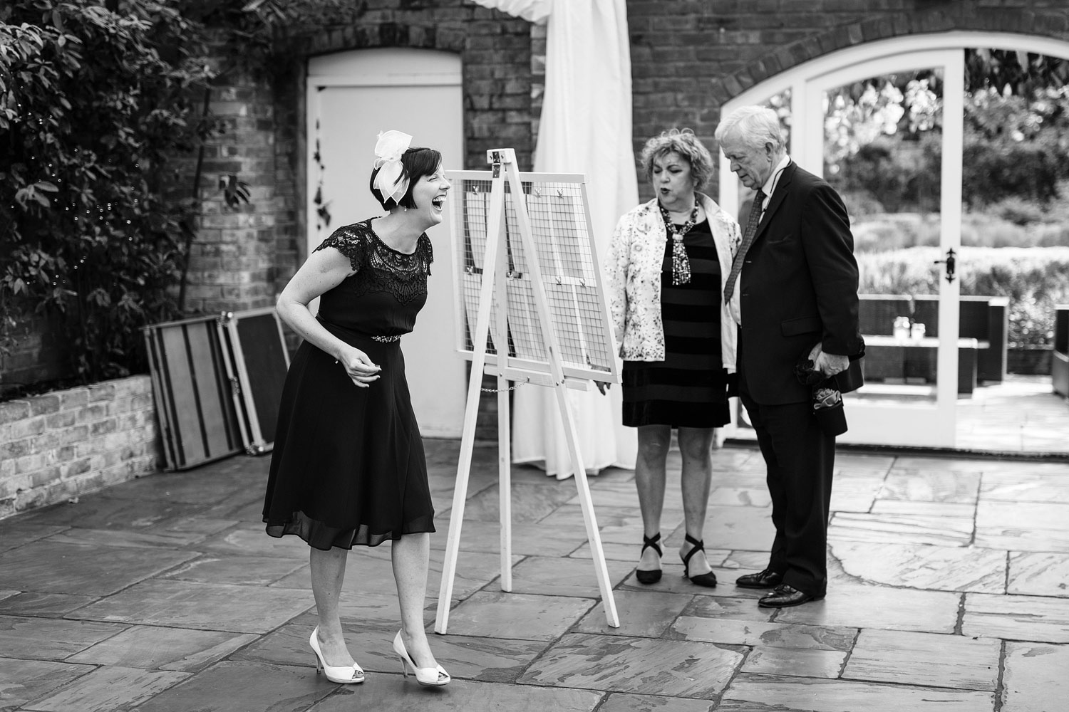Guests at a wedding laugh at the table plan at Northbrook Park - London wedding photographer