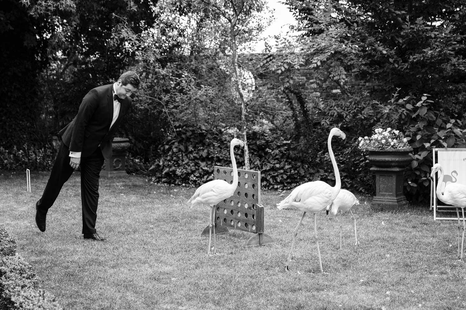 A groomsman pretends to be a flamingo at the wedding at the Roof Gardens - London wedding photographer