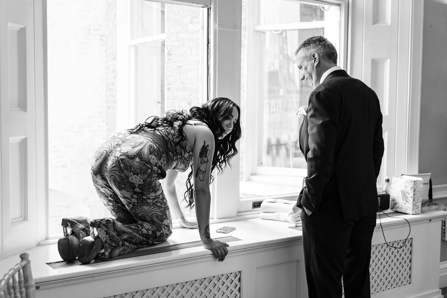 The bride's sister climbs onto a window sill at an Asia House wedding - London wedding photographer