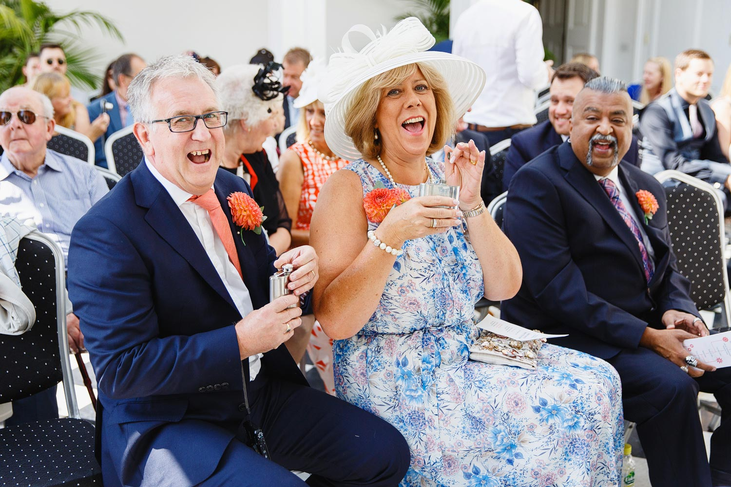 Parents of the groom drink from hip flasks before a wedding at York House in Twickenham.