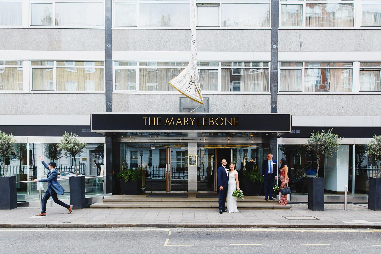 The bride and groom wait for a taxi outside the Marylebone Hotel - London wedding photographer