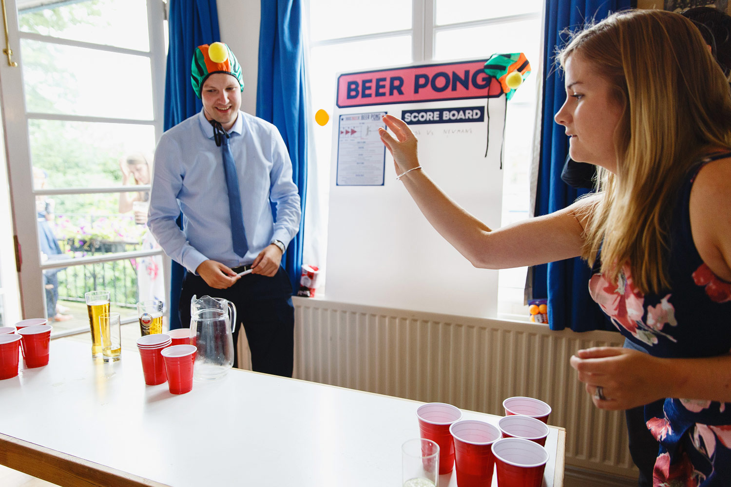Guests play beer pong at the wedding at Twickenham Rowing Club - London wedding photographer