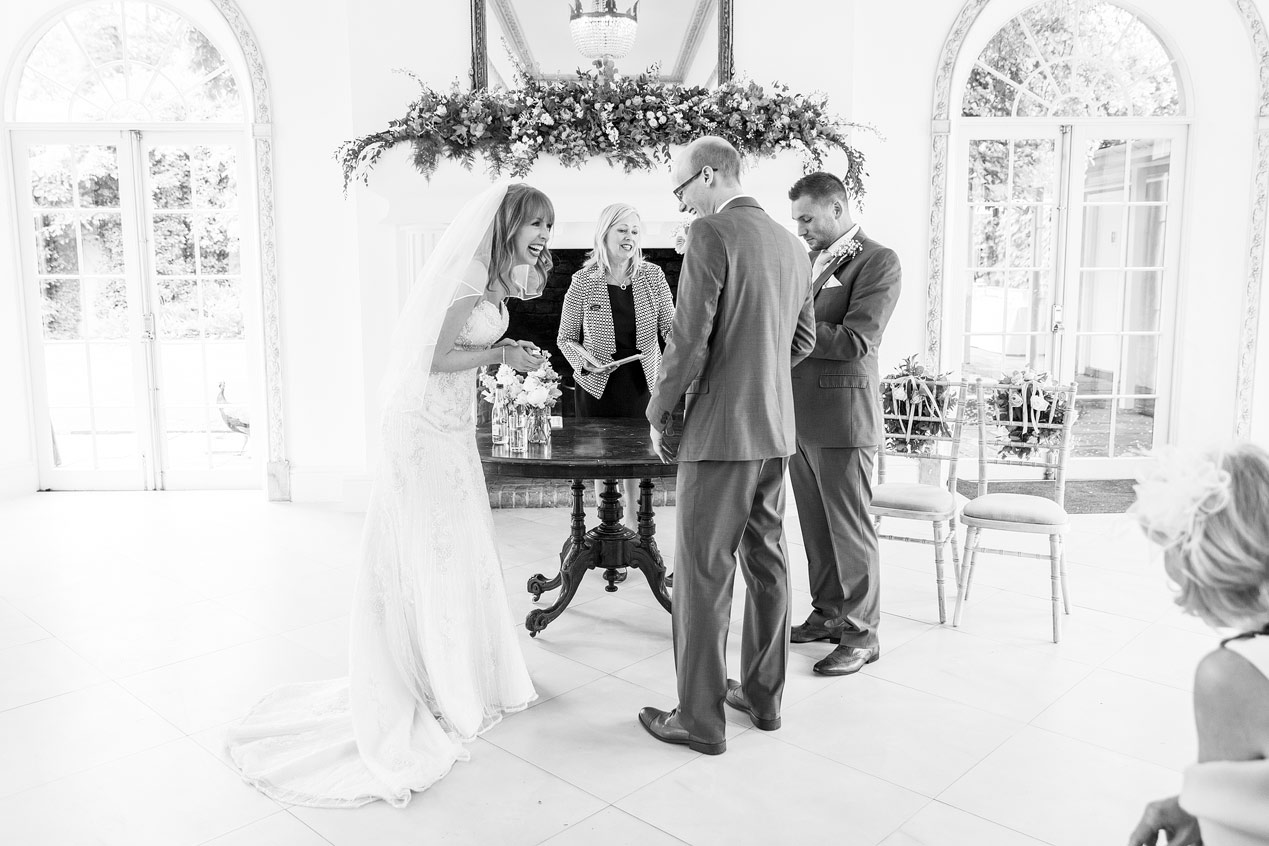 A couple laugh at their Northbrook Park wedding ceremony - London wedding photographer