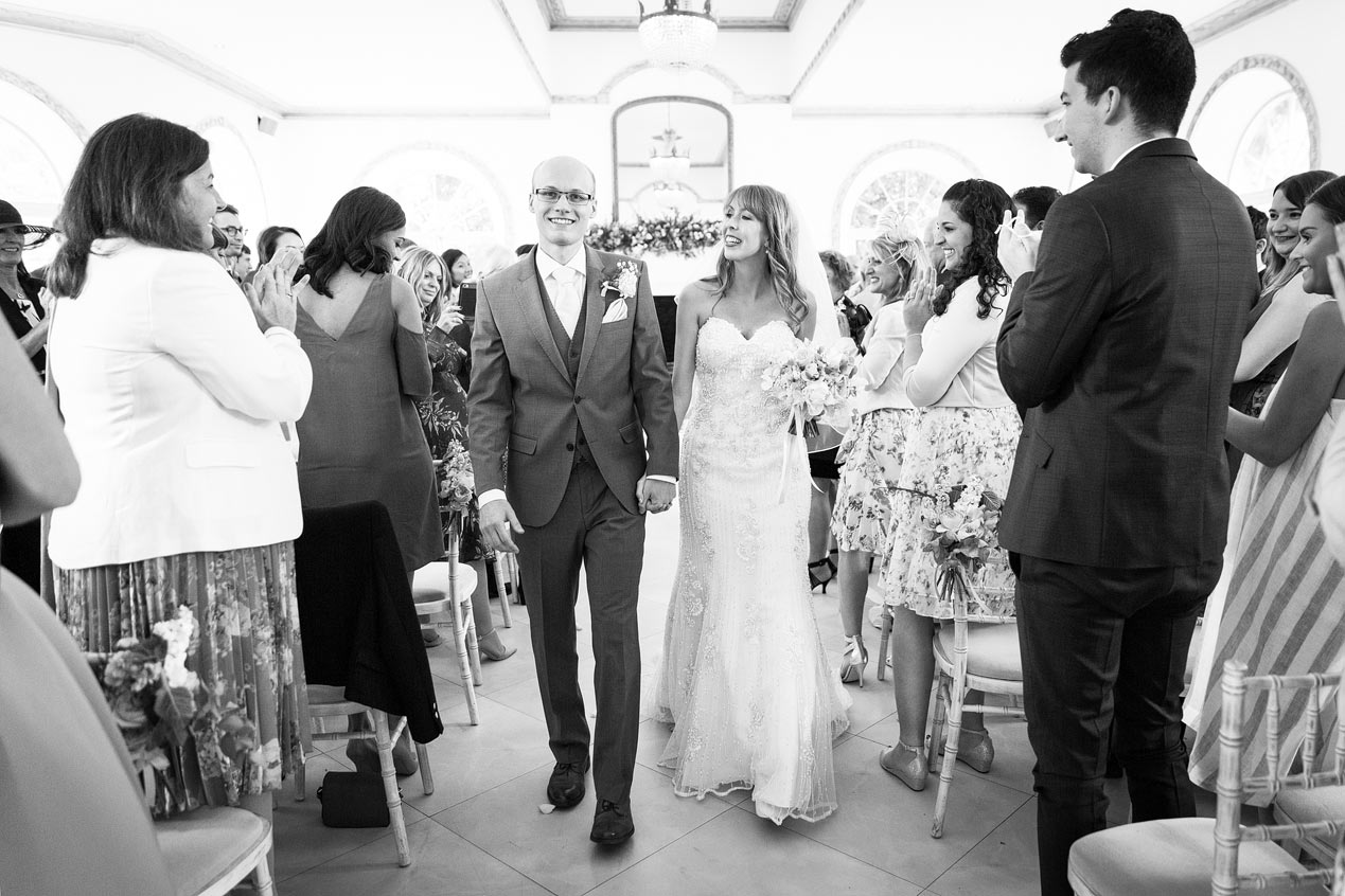 A couple walk back down the aisle at their Northbrook Park wedding ceremony - London wedding photographer