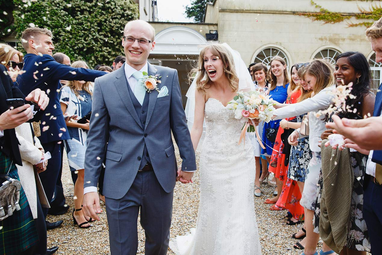 Guests throw confetti at their Northbrook Park wedding ceremony - London wedding photographer