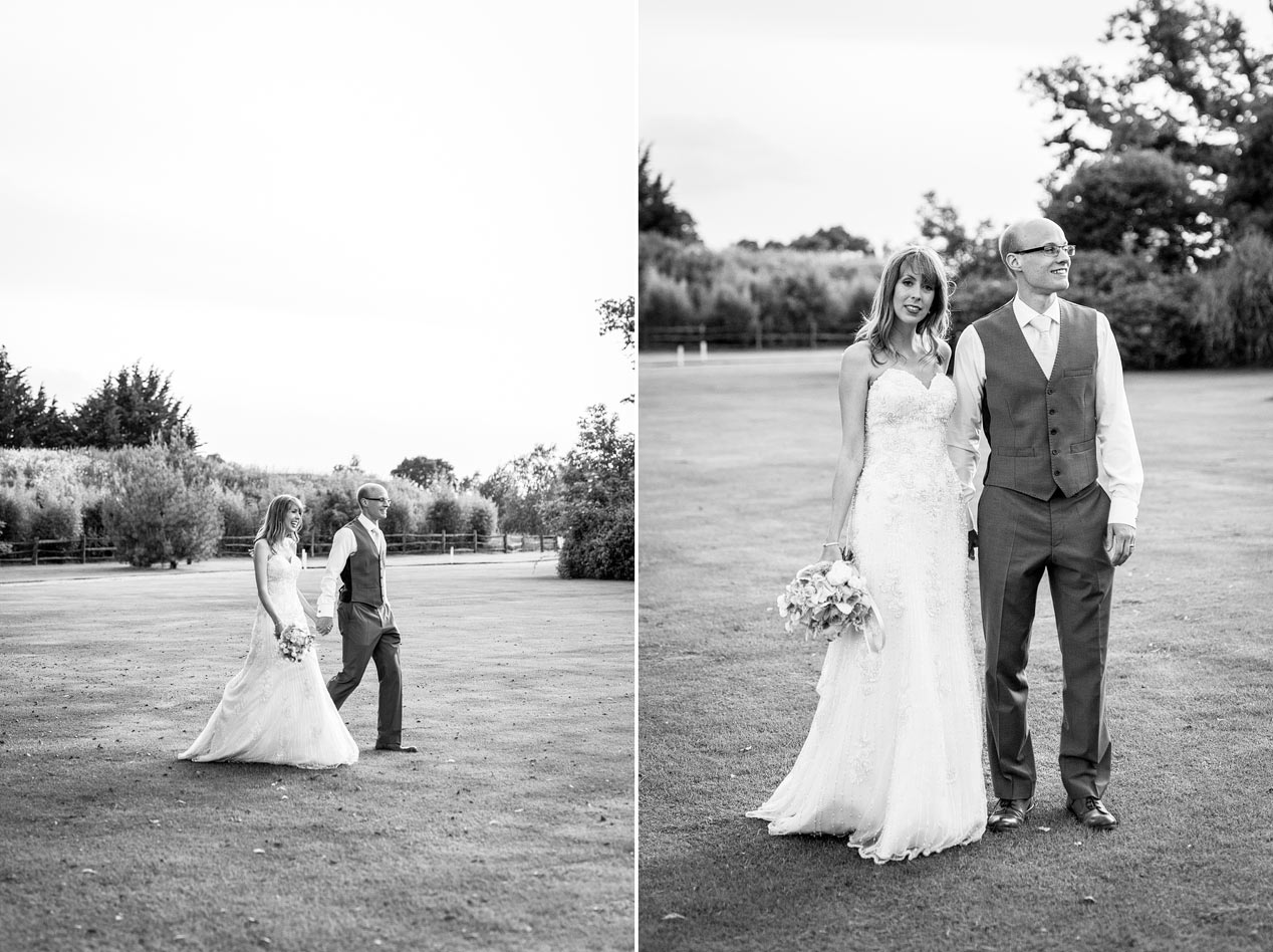 A black and white photograph of a couple pose for photographs at their Northbrook Park wedding ceremony - London wedding photographer