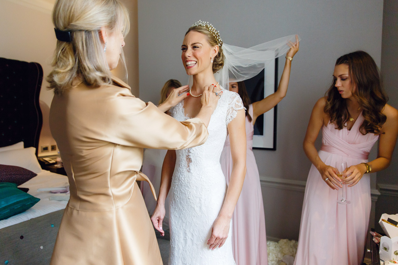 A bride gets dress on at the Ampersand Hotel - London wedding photographer - Ulrich Engler bridal gown