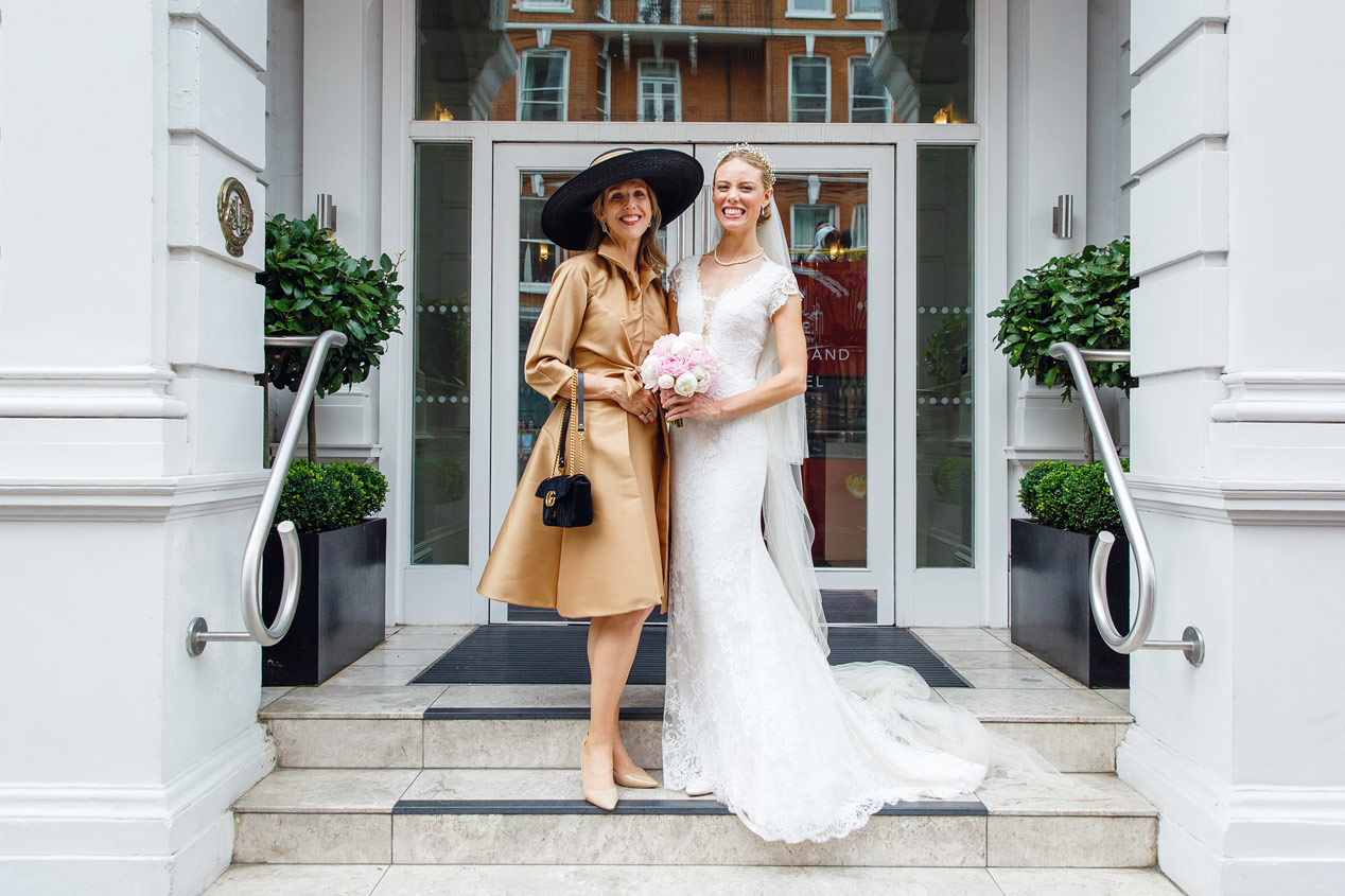A bride and her mother pose outside the Ampersand Hotel in Kensington London.