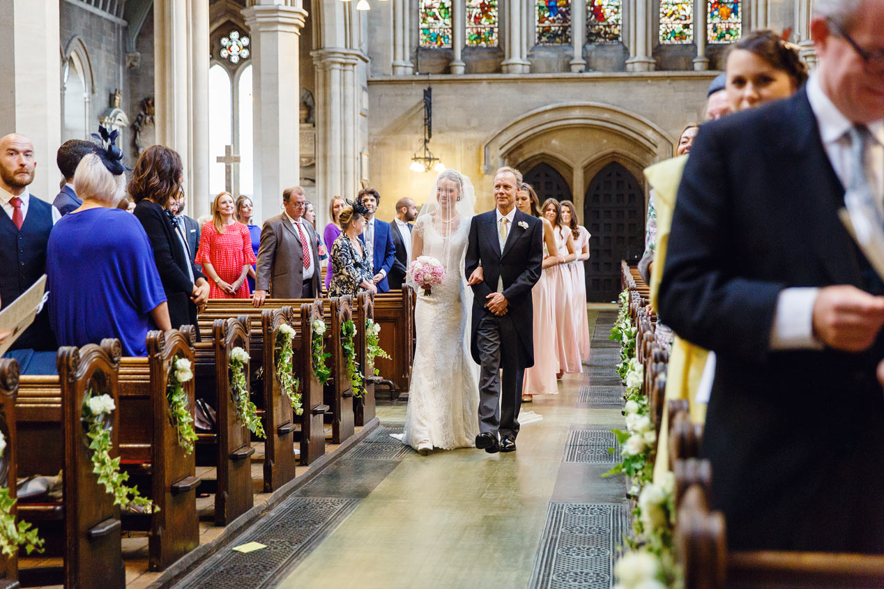 A bride and her father walk down the aisle at the St Mary Abbots church in Kensington London.