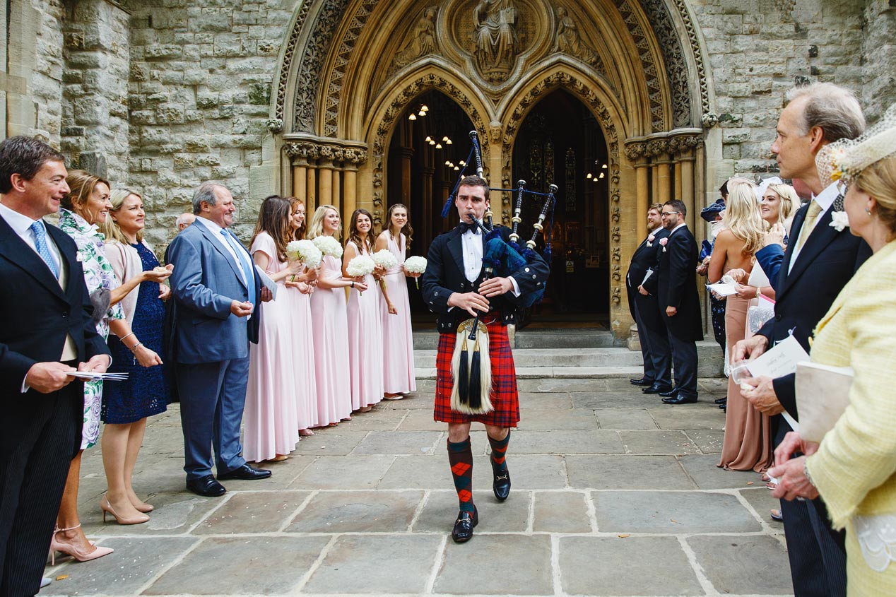 A bagpiper announces the couple as they exit the St Mary Abbots church in Kensington, London